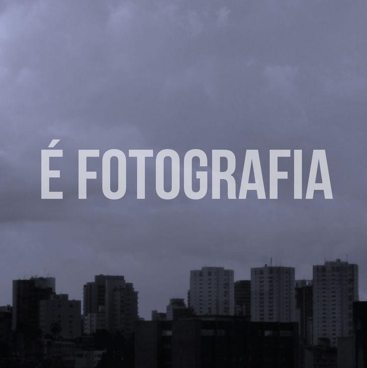 """Imagem de prédios e de um céu cinzento. Centralizado, texto """"É Fotografia""""."""